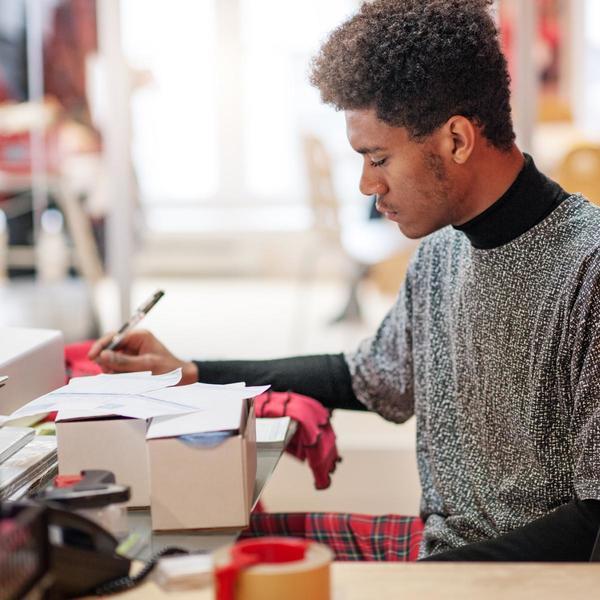 Uomo scrive su un pacco